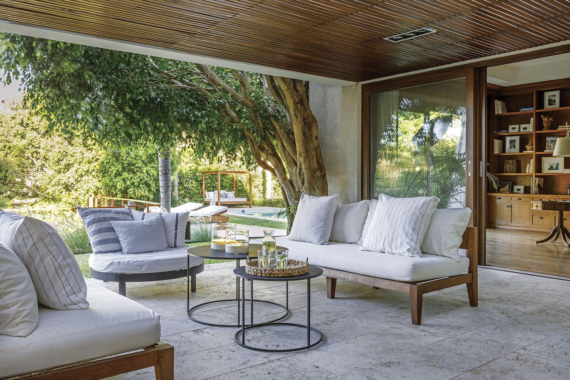 Grandes aberturas de PCV foliado símil madera con DVH (Perfiles y Servicios) integran este espacio con piso de Travertino rústico. Velas (Bohemia Velas).
