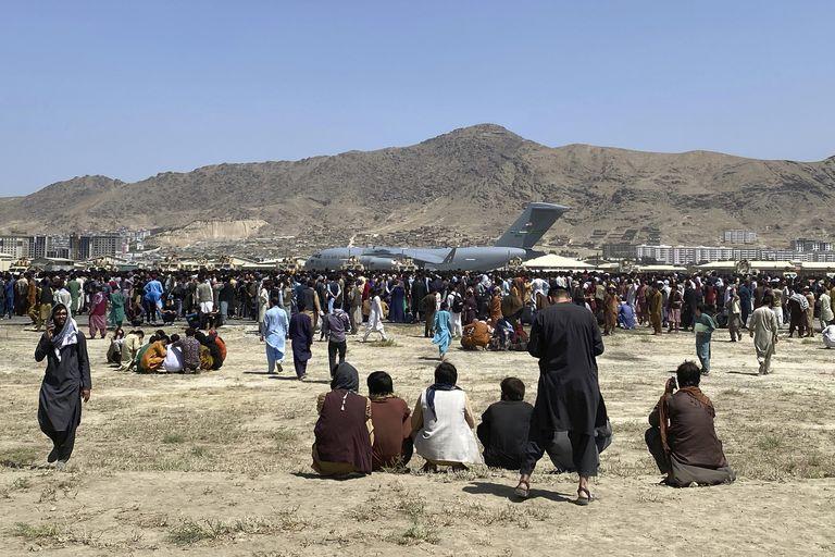 Cientos de personas esperan junto a un avión de transporte C-17 de la Fuerza Aérea de Estados Unidos en el perímetro del aeropuerto internacional de Kabul, Afganistán. Facebook y WhatsApp son las principales plataformas digitales que utilizan los residentes para gestionar sus trámites de visas, muchas veces sin saber quiénes están detrás de estos formularios o cuentas