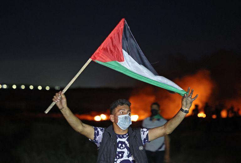 Un palestino flamea una bandera en medio de la creciente tensión en la frontera entre Gaza e Israel