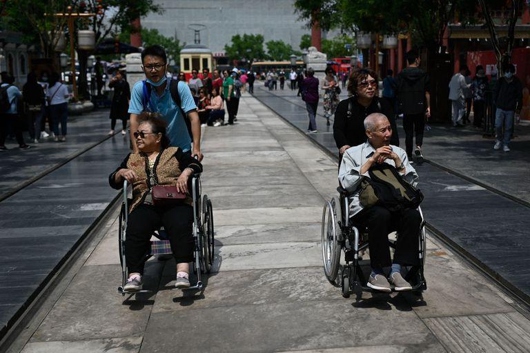 Un anciano y una mujer son empujados en sillas de ruedas a lo largo de una calle en Beijing.