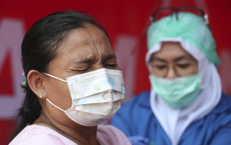 Una mujer recibe la vacuna de AstraZeneca durante una campaña de vacunación masiva para trabajadores del transporte público en la terminal de autobús de Kampung Rambutan en Yakarta, Indonesia, el jueves 10 de junio de 2021. (AP Foto/Achmad Ibrahim)