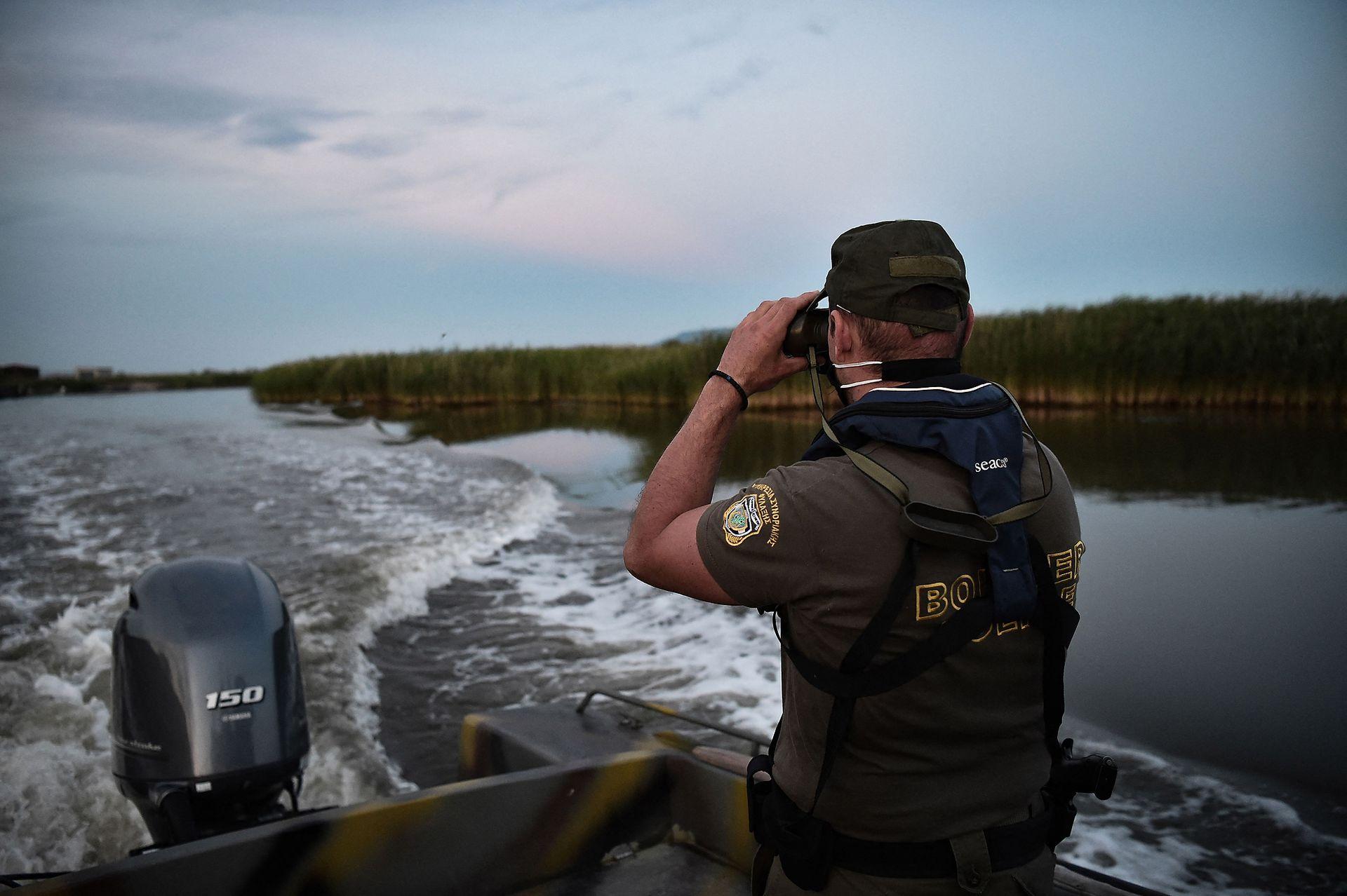 El sol se pone sobre el delta del Evros, la frontera fluvial entre Grecia y Turquía, cuando dos guardias griegos comienzan sus rondas diarias para evitar que los migrantes entren ilegalmente por el río