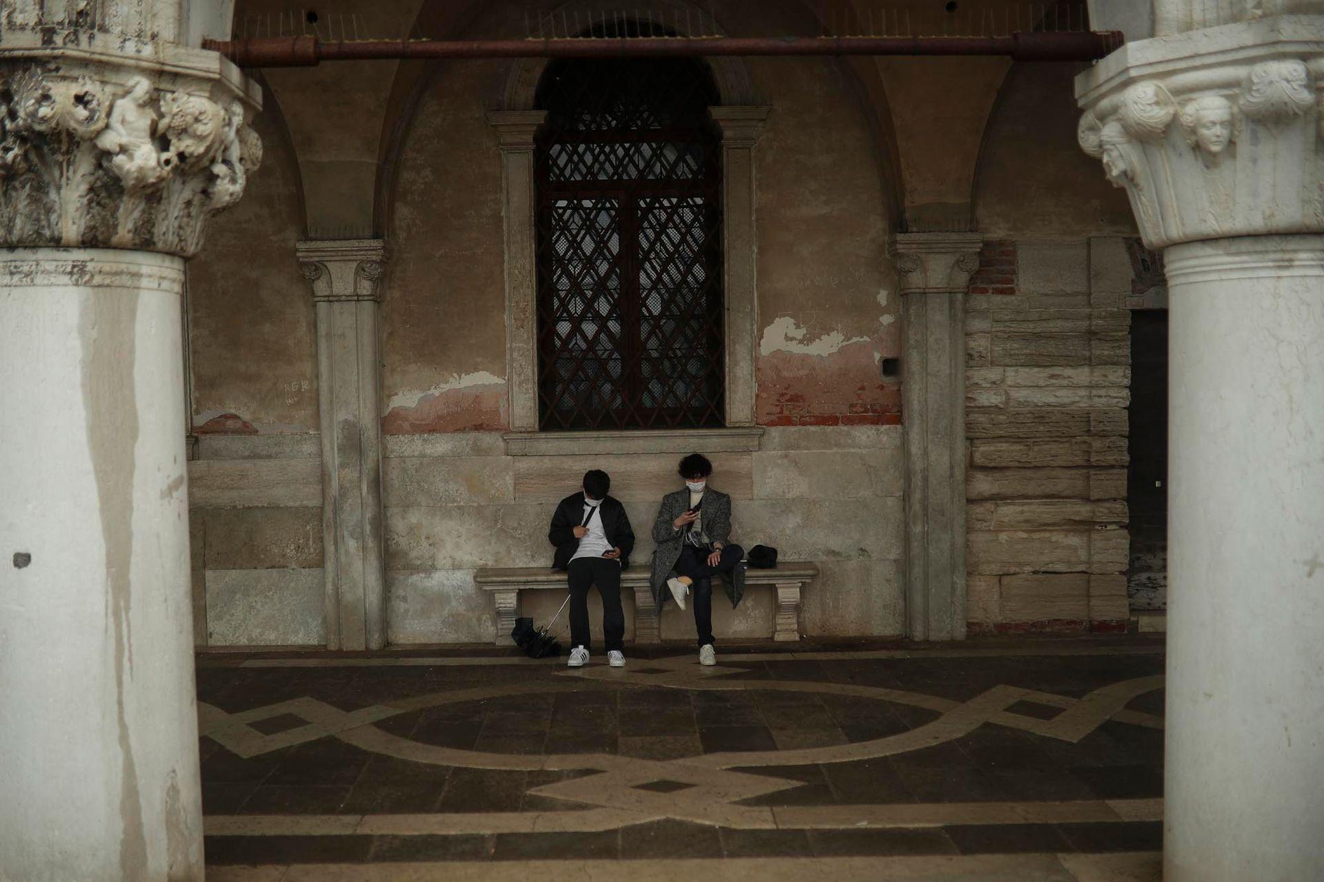 Turistas con barbijos miran sus celulares mientras descansan en la plaza de San Marcos en Venecia, el domingo 1 de marzo de 2020.