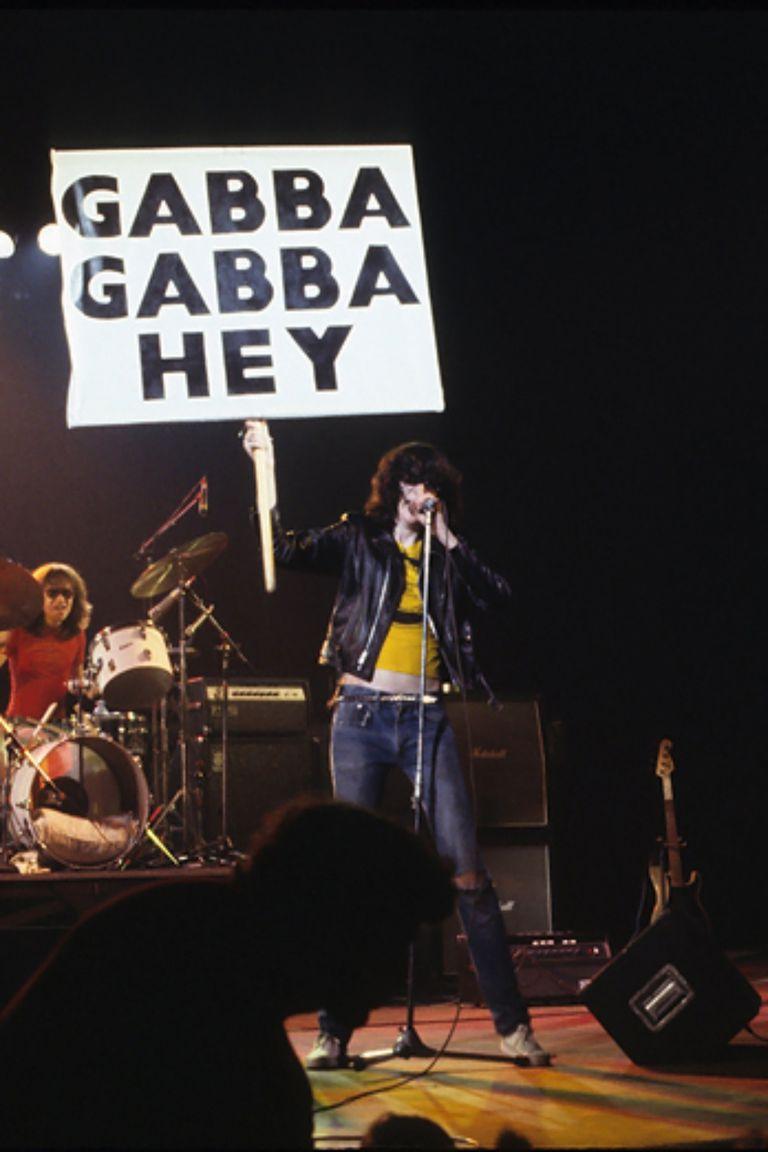 """Joey Ramone sostiene un carte de """"Gabba Gabba Hey"""" durante un show de Ramones"""