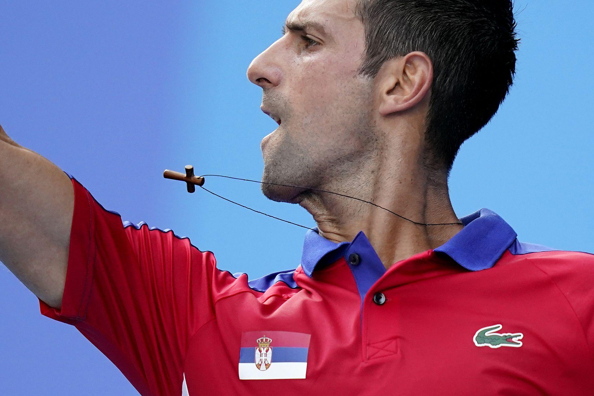 Un collar cuelga del cuello de Novak Djokovic cuando regresa a Hugo Dellien, de Bolivia, durante la competencia de tenis en los Juegos Olímpicos de Verano de 2020, el sábado 24 de julio de 2021 en Tokio, Japón.