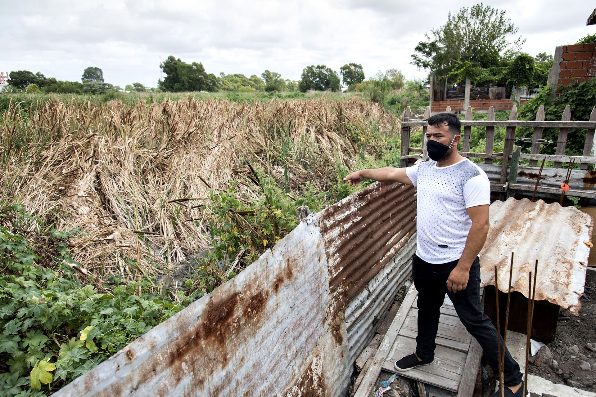 Miguel Dávalos, vecino del barrio, muestra cómo algunas casas del barrio están directamente afectadas por el terreno lindero