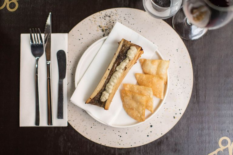 Médula de llama rostizada con puré de berenjenas asadas y chips crocantes, un plato que se puede comer en Finca.