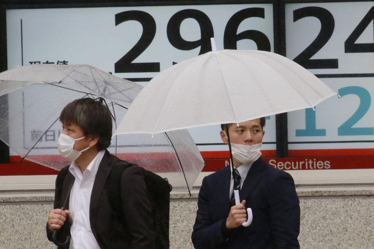 Personas frente a una cartelera financiera en Tokio el 14 de abril del 2021. (Foto AP/Koji Sasahara)
