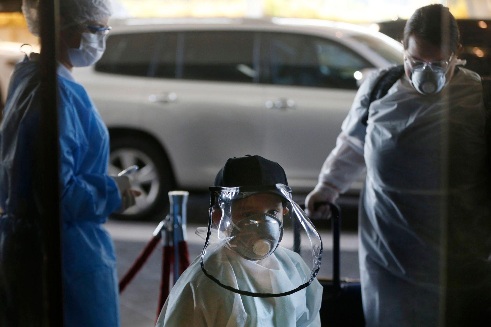 Matias Morel y su tía Stefanie Ruiz Díaz, pasan un punto de control de temperatura a su llegada al aeropuerto Silvio Pettirossi en Luque para tomar un vuelo a Miami