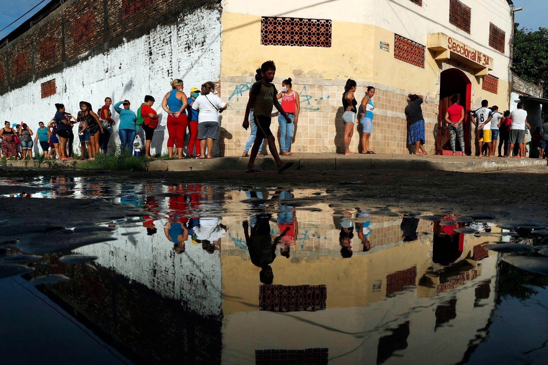 Los vecinos hacen fila para obtener alimentos básicos gratuitos fuera de la escuela primaria de Santa Ana