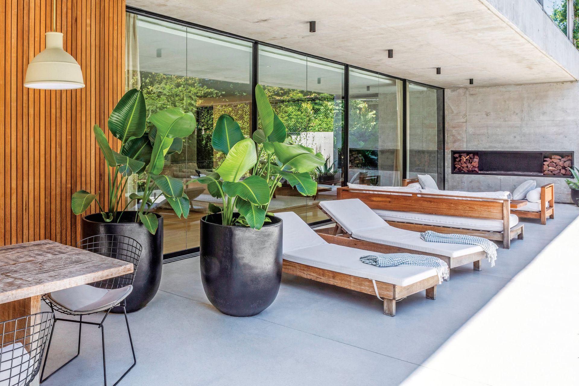 Juego de living de exterior hecho a medida, reposeras en lapacho (todo de Estudio LDMB) y macetas de fibra de vidrio (Herbario).