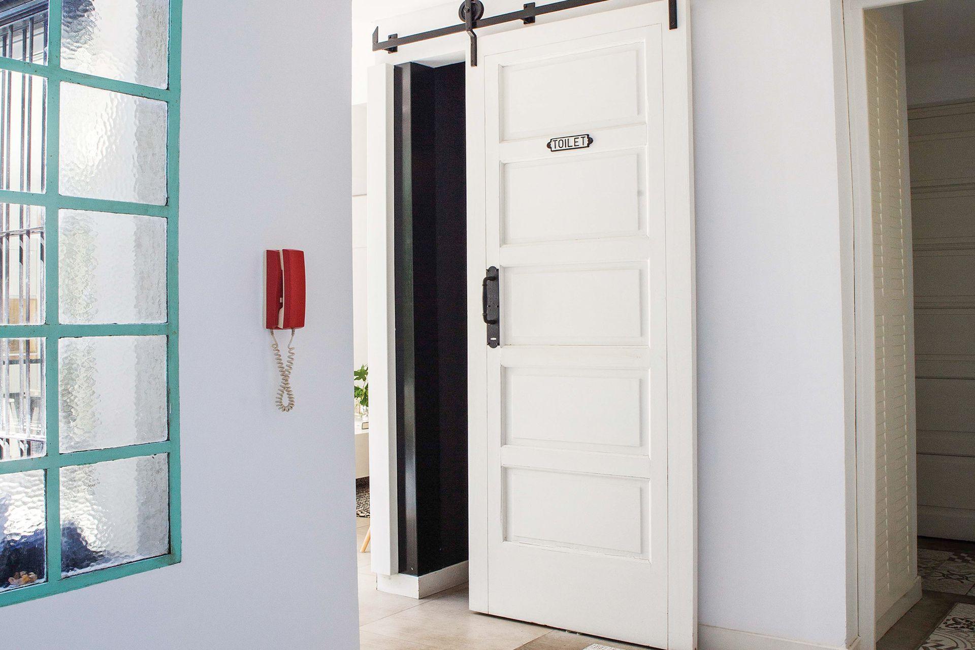 Contigua al hall, una puerta que corre sobre rieles de hierro lleva al toilette.