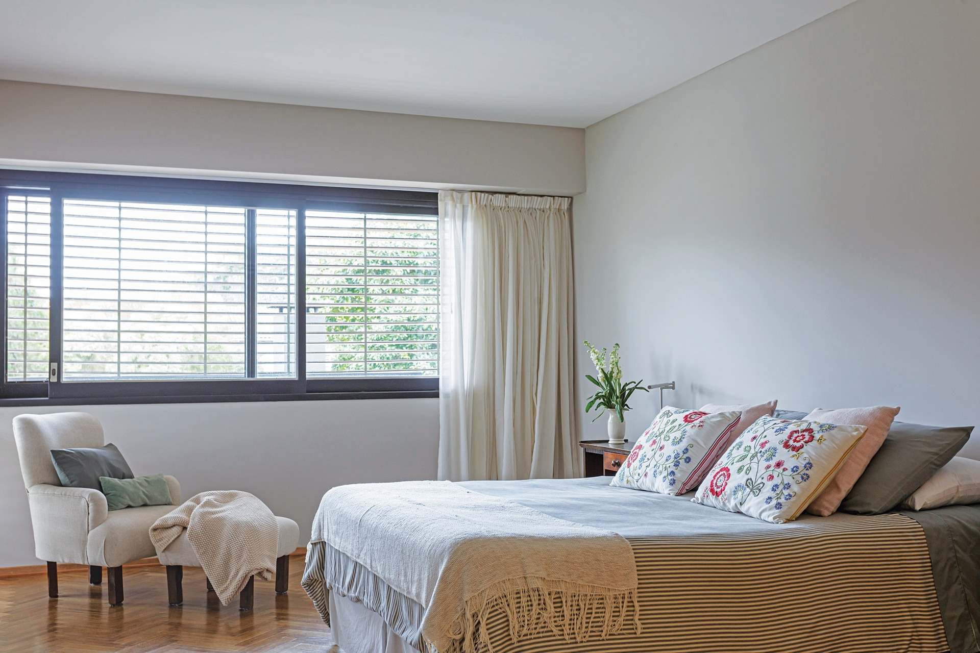 Sillón con apoyapiés y la cama con cover de algodón (Pottery Barn), almohadones bordados (Zara Home) y pie de lana (Galpón Chic).