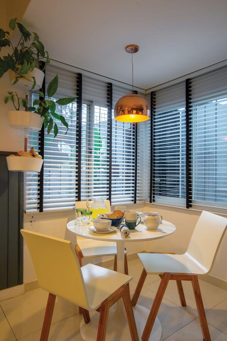 Al desayunador, con muebles contemporáneos, se le sumó un par de cortinas americanas con tiras negras y una jardinera colgante con kokedamas.