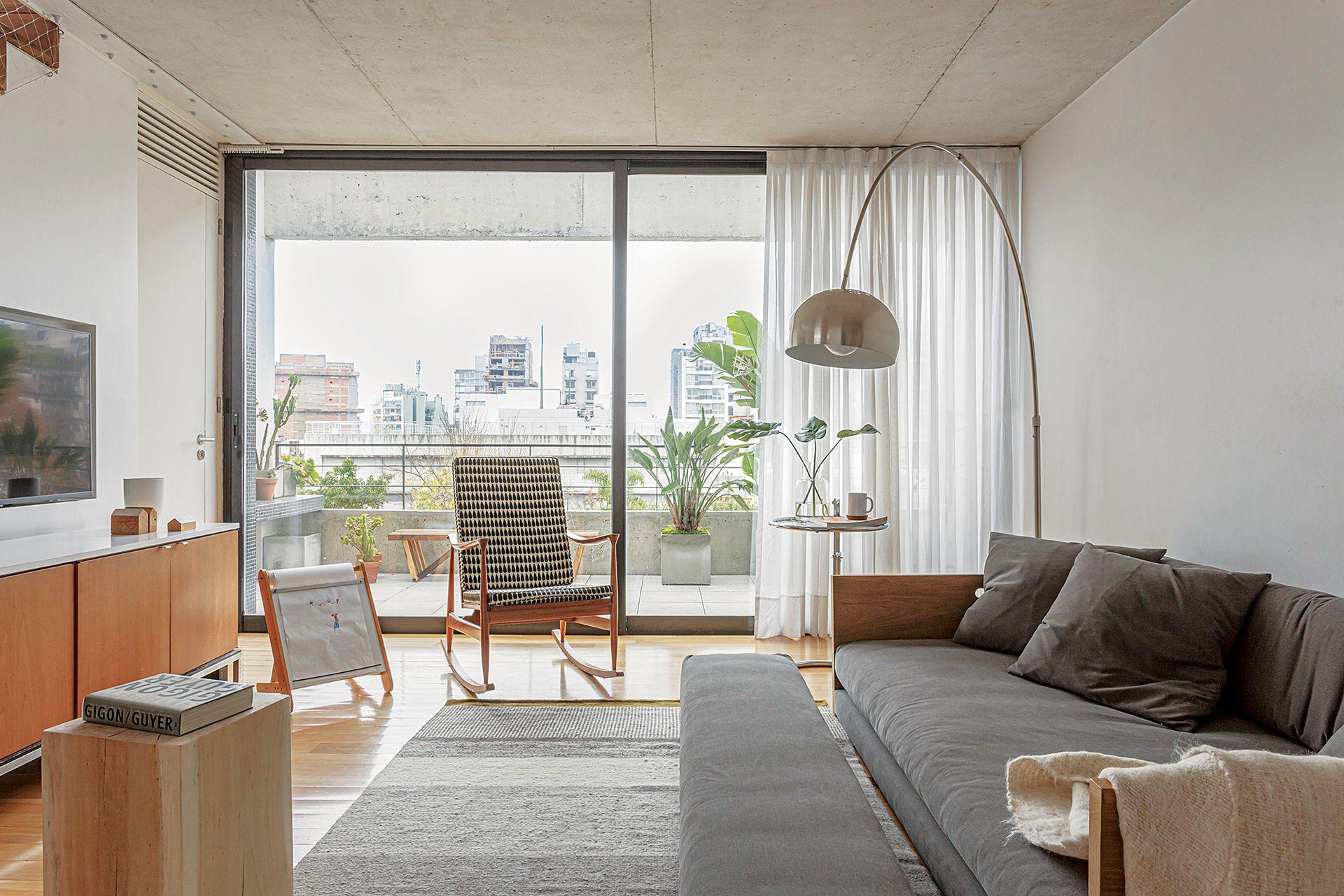 Sillón 'Petiso' de 2x1,20m con estructura de madera y apoyapiés (Helmut) tapizado (Fluoh Objetos Textiles). Alfombra a rayas (Elementos Argentinos).