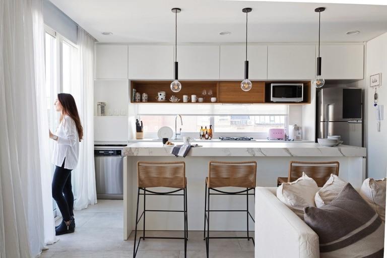 En esta obra del estudio DIPA, la isla se pensó como el punto central del ambiente integrado. Por eso las cortinas (Tienda Mayor) siguen una estética elegante (pero práctica) en la cocina.