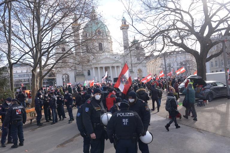 Policías junto a manifestantes sosteniendo banderas austriacas durante una protesta contra las restricciones y medidas adoptadas por el gobierno de Austria para combatir el nuevo coronavirus, el 13 de febrero de 2021 en Viena