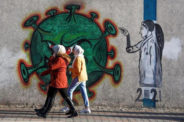 Mujeres palestinas pasan al lado de un mural de una enfermera que inyecta la vacuna contra el Covid-19 en la Ciudad de Gaza, el 31 de diciembre de 2020