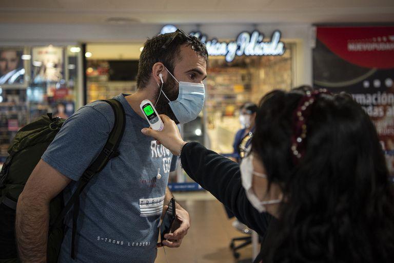 A un pasajero le toman la temperatura en el Aeropuerto Internacional Arturo Merino Benítez, en Santiago de Chile
