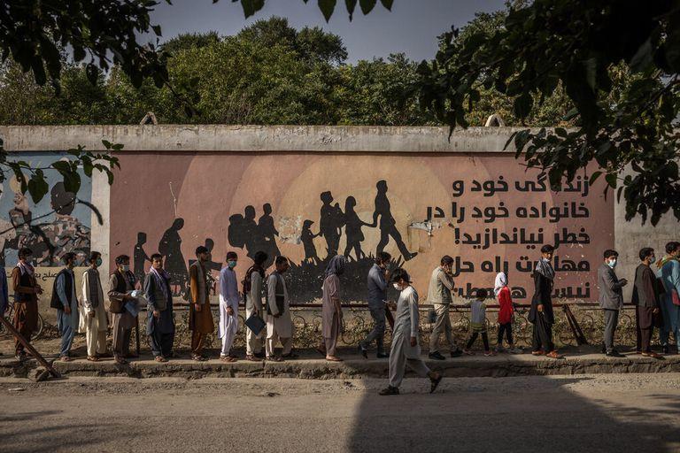 Un mural de advertencia contra la migración sirvió de telón de fondo para las personas que hacían cola frente a la oficina de pasaportes en Kabul.