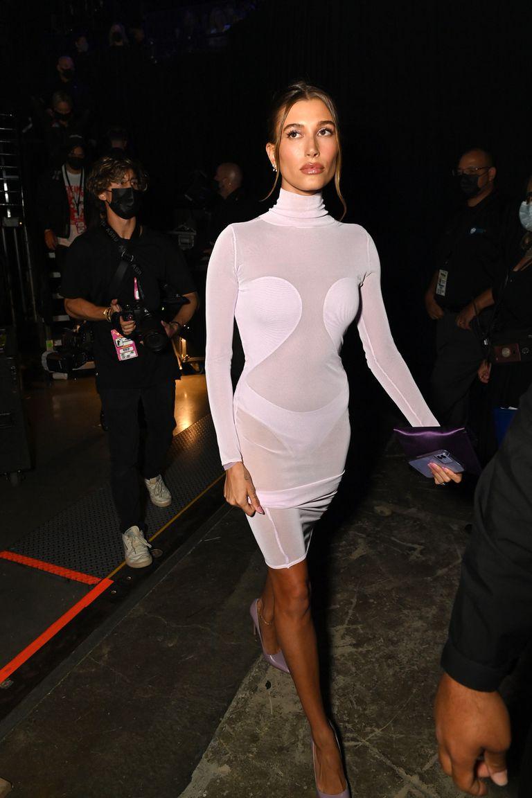 Hailey Bieber acompañó a su esposo y eligió un modelo corto en color gris, con cuello y mangas, que hacía resaltar su figura, entre trasparencias