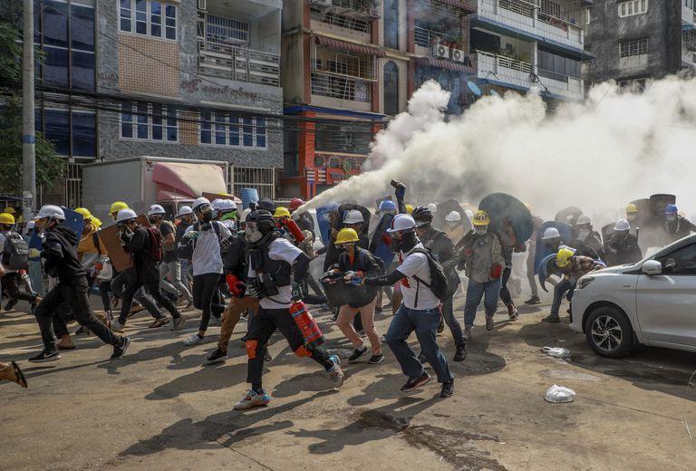 Los manifestantes corren en la ciudad de  Yangon, Myanmar, tras una embestida de las fuerzas de seguridad