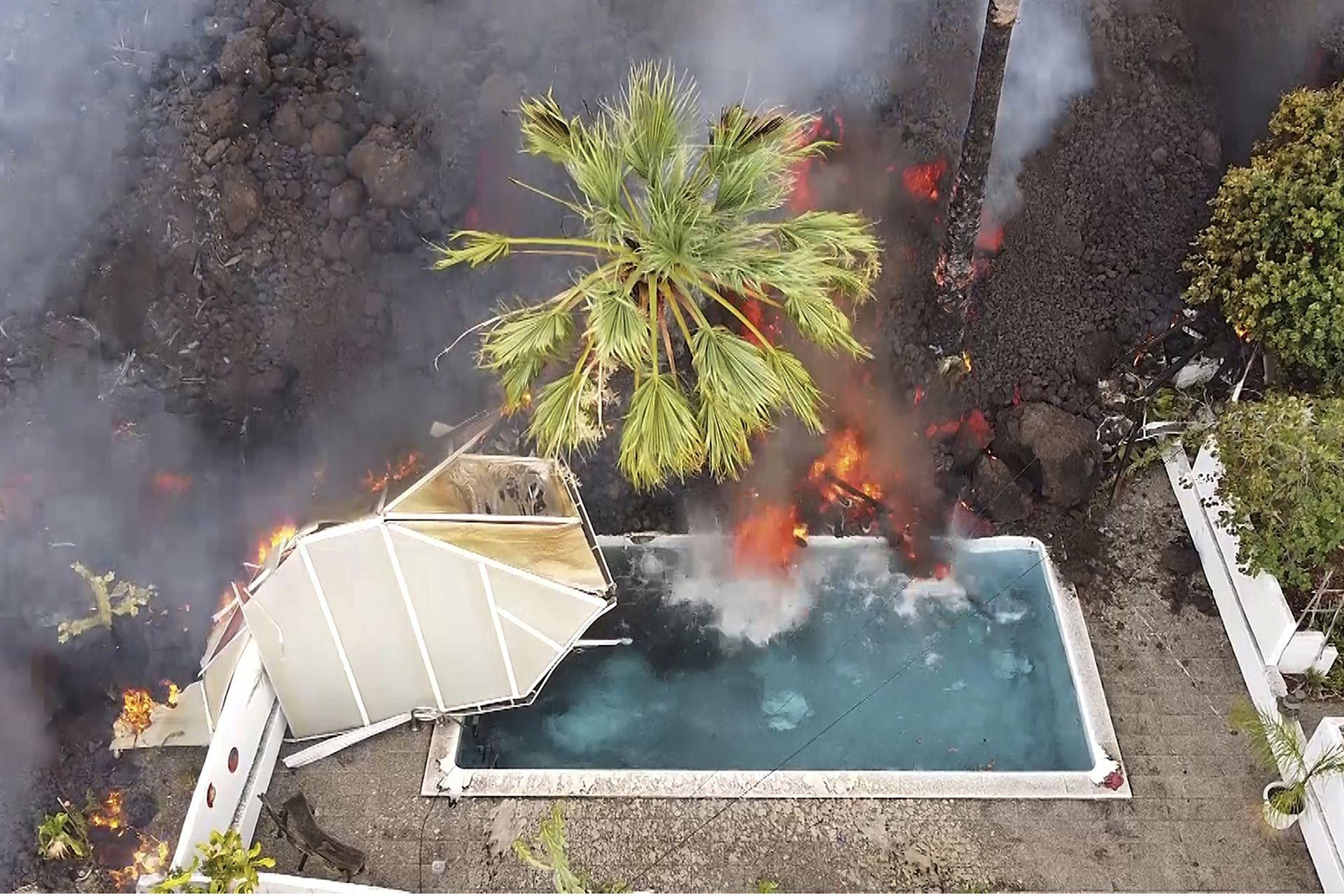 Lenta pero implacablemente la lava entra en la piscina de una casa que ya desapareció