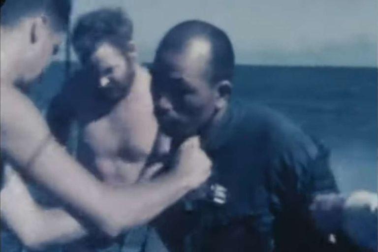 Soldados estadounidenses rescataron de una balsa a un hombre y lo revisan sobre la cubierta de un barco