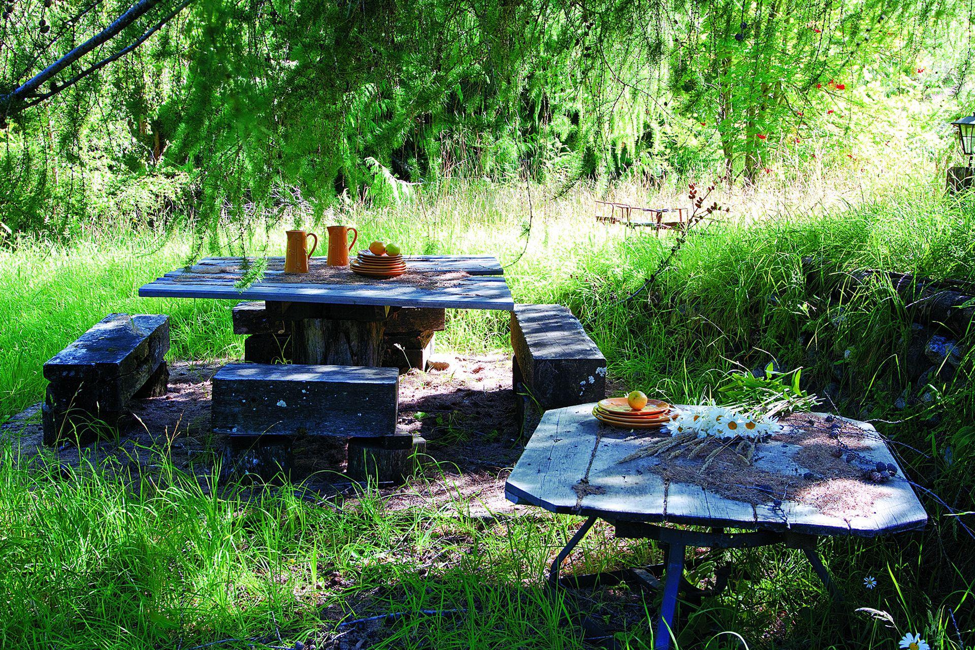 En la parte más silvestre del jardín, zona de reunión y descanso alrededor de una mesa con bancos de madera.