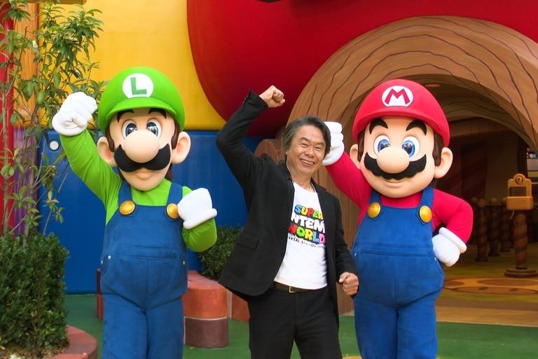 Shigeru Miyamoto con Luigi y Mario, sus creaciones, en la entrada de Super Nintendo World