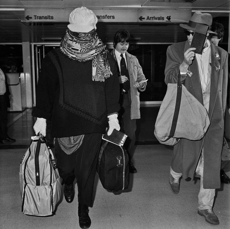 Boy George llega al aeropuerto de Heathrow en 1985 cubriéndose la cara con una bufanda.