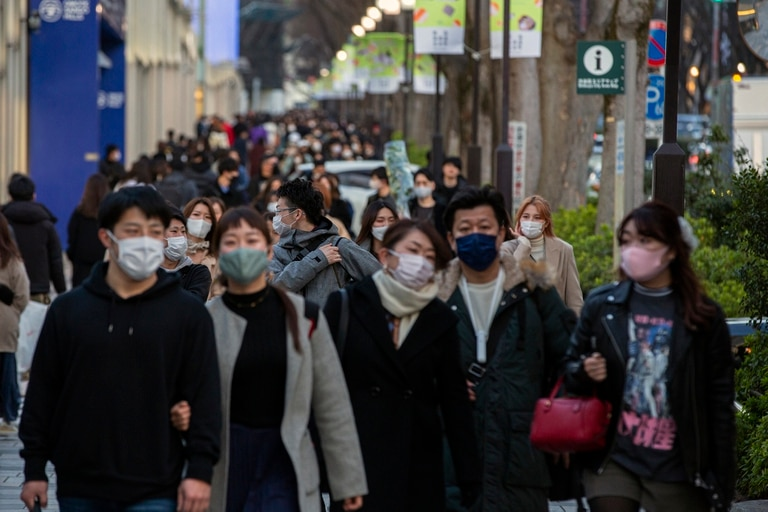 Personas con tapabocas para ayudar a frenar la propagación del coronavirus caminan por una vereda en un distrito comercial de Tokio, el domingo 28 de febrero de 2021
