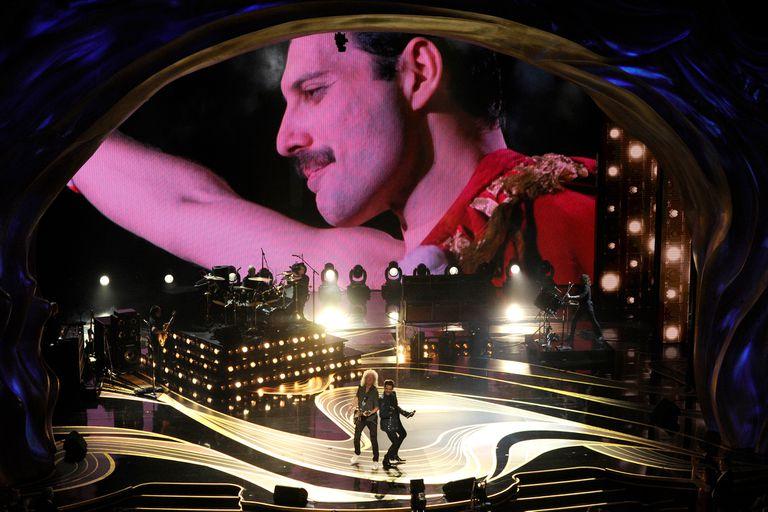 Queen con Adam Lambert y una imagen de Freddie Mercury de fondo