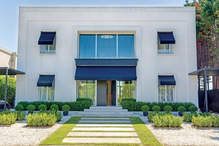 Simetría perfecta en la fachada, donde el blanco impecable se corta con los toldos y las macetas negras.