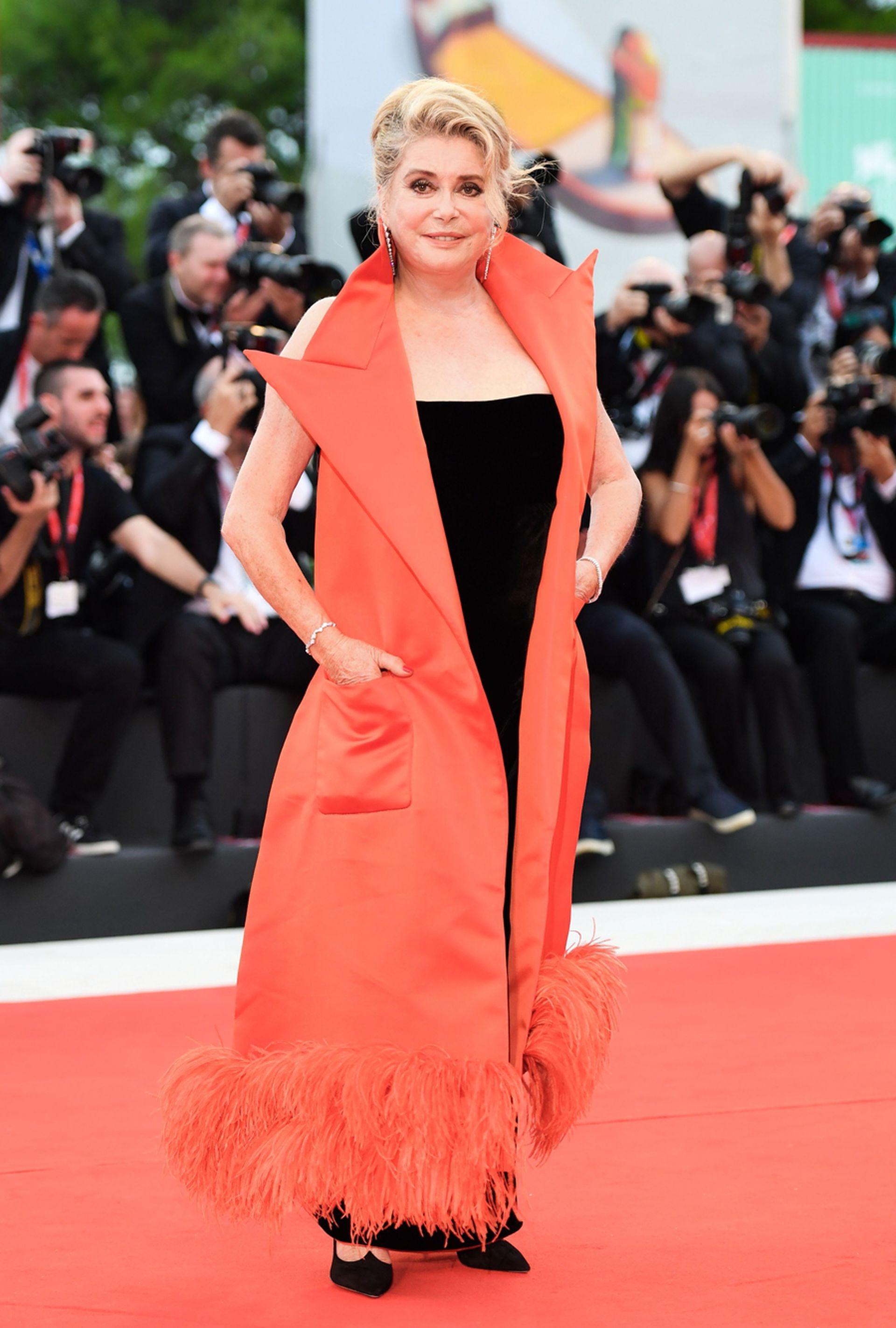 Deneuve recurrió al siempre ocurrente Jean Paul Gaultier: vestido de terciopelo negro con escote recto y maxi chaleco de satén naranja con detalle de plumas