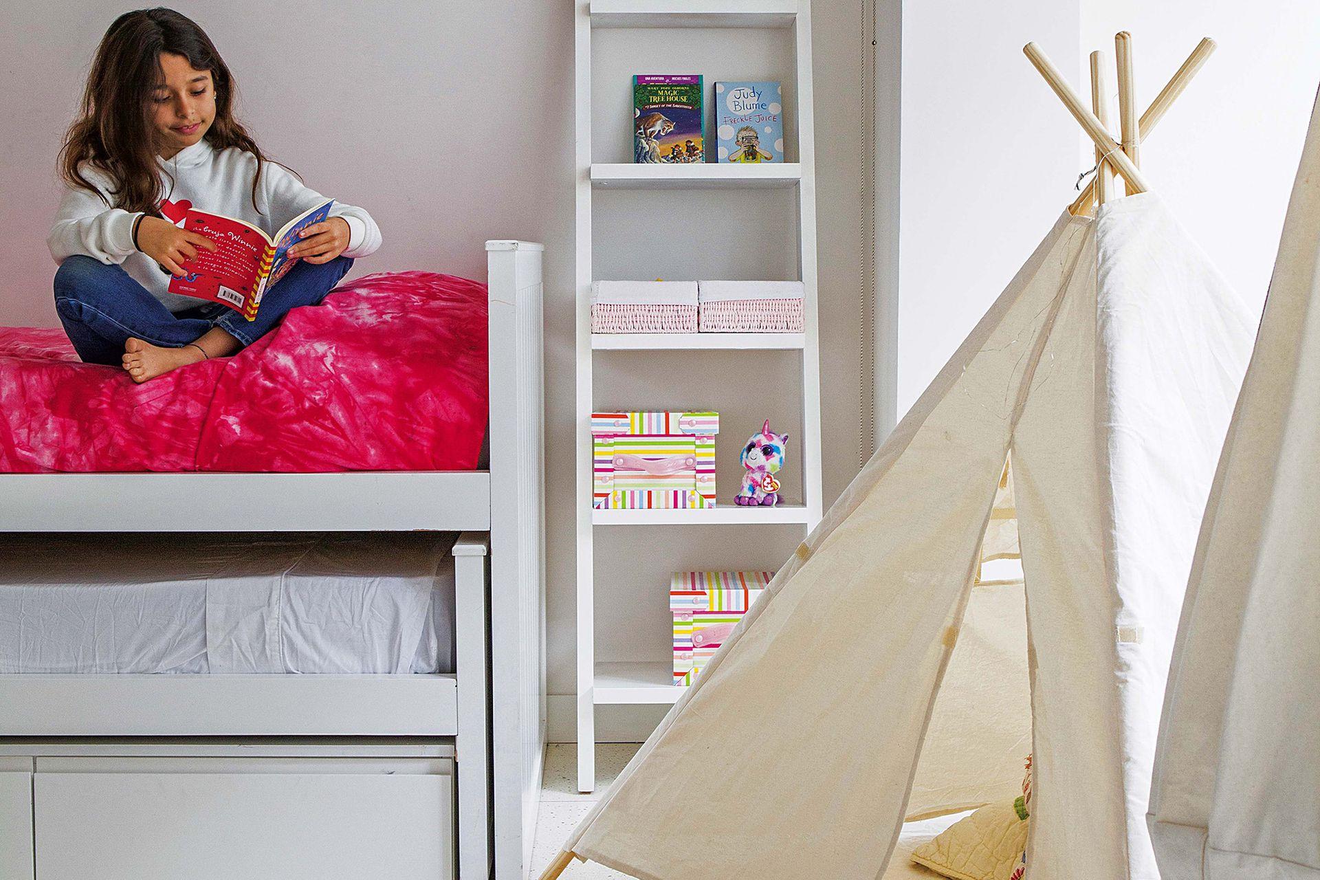 Al lado de la cama, biblioteca y carpa infantil.