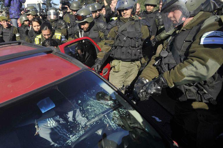El bastón del gendarme atraviesa el vidrio del auto; atrás la sacan a Victoria