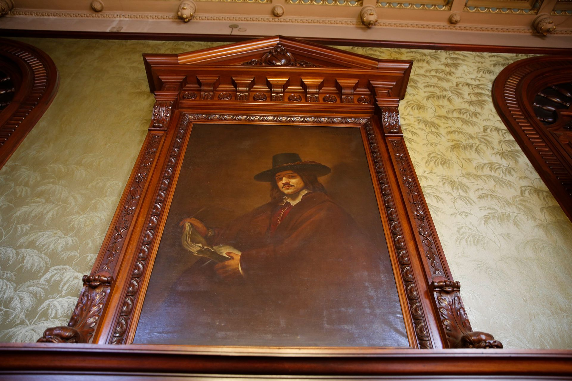 Copia de un autorretrato de Rembrandt, con un libro en la mano, en vez de una paleta o un pincel. Realizado por el italiano Nazareno Orlandi, quien también hizo los frescos del Gran Spendid