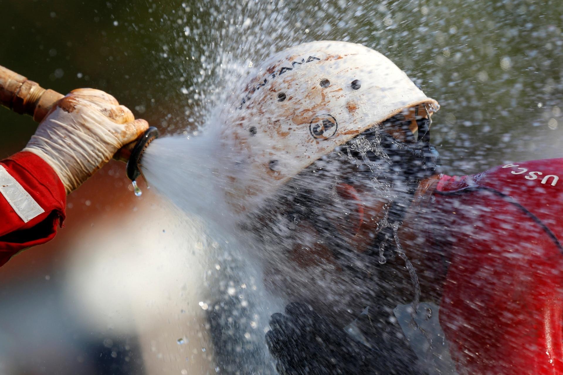 Rocían con agua a un miembro del equipo de rescate para eliminar el lodo, al regresar de la misión, luego del colapso de un depósito de relaves propiedad de la empresa minera brasileña Vale SA, en Brumadinho, Brasil, el 27 de enero.