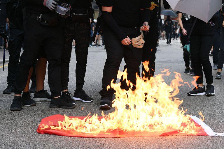 Manifestantes queman la bandera china, símbolo de la revolución