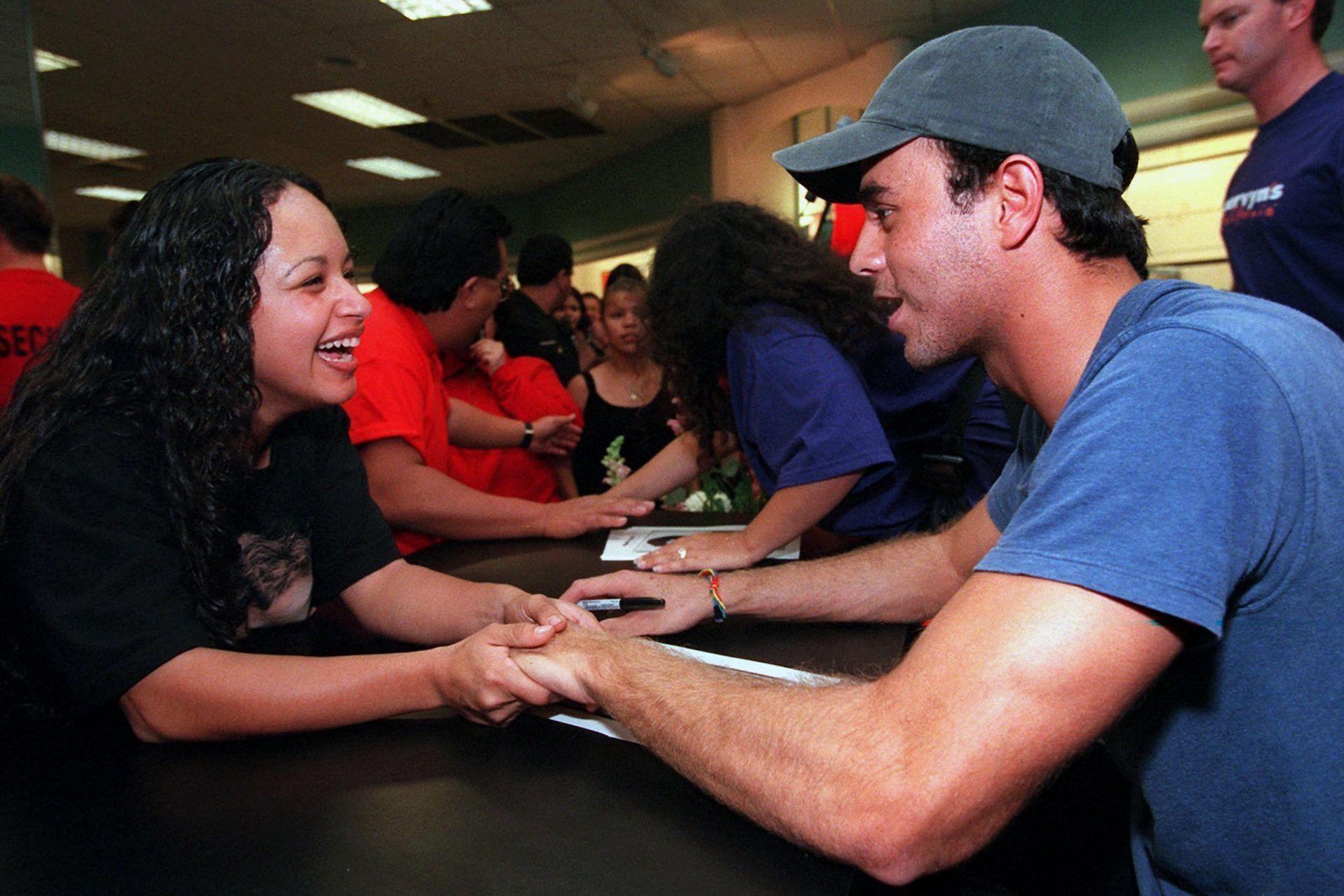 Enrique Iglesias charla con una fan, durante un encuentro en Montebello, California, el 25 de noviembre de 1997