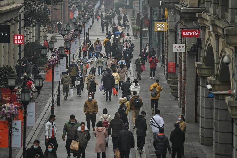 La gente camina por una calle peatonal en Wuhan, provincia central de Hubei en China, el 23 de enero de 2021, un año después de que la ciudad se cerrara para frenar la propagación del coronavirus