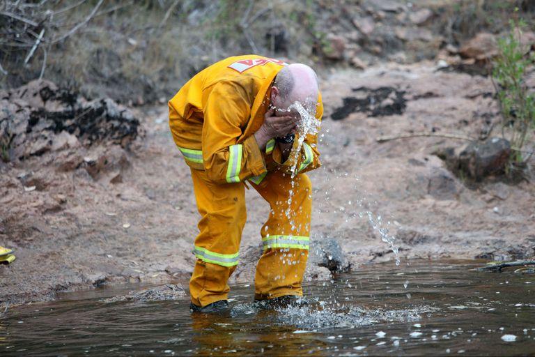 Un bombero se lava la cara en el Alpine National Park