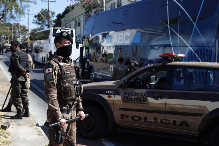Policías militares brasileños montan guardia junto al autobús del equipo argentino de fútbol Boca Juniors, estacionado junto a una estación policial en Belo Horizonte, el miércoles, 21 de julio del 2021, al día siguiente de que el equipo fue eliminado de la Copa Libertadores. (AP Foto/Bruna Prado)