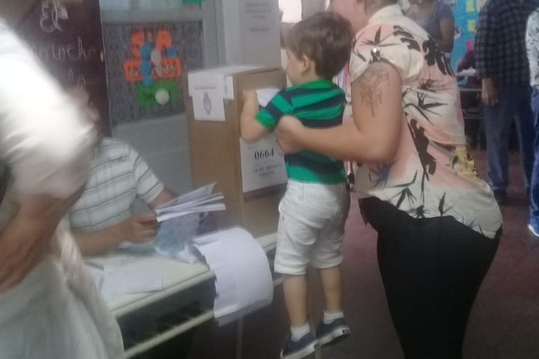 Un niño mete un sobre en una urna.