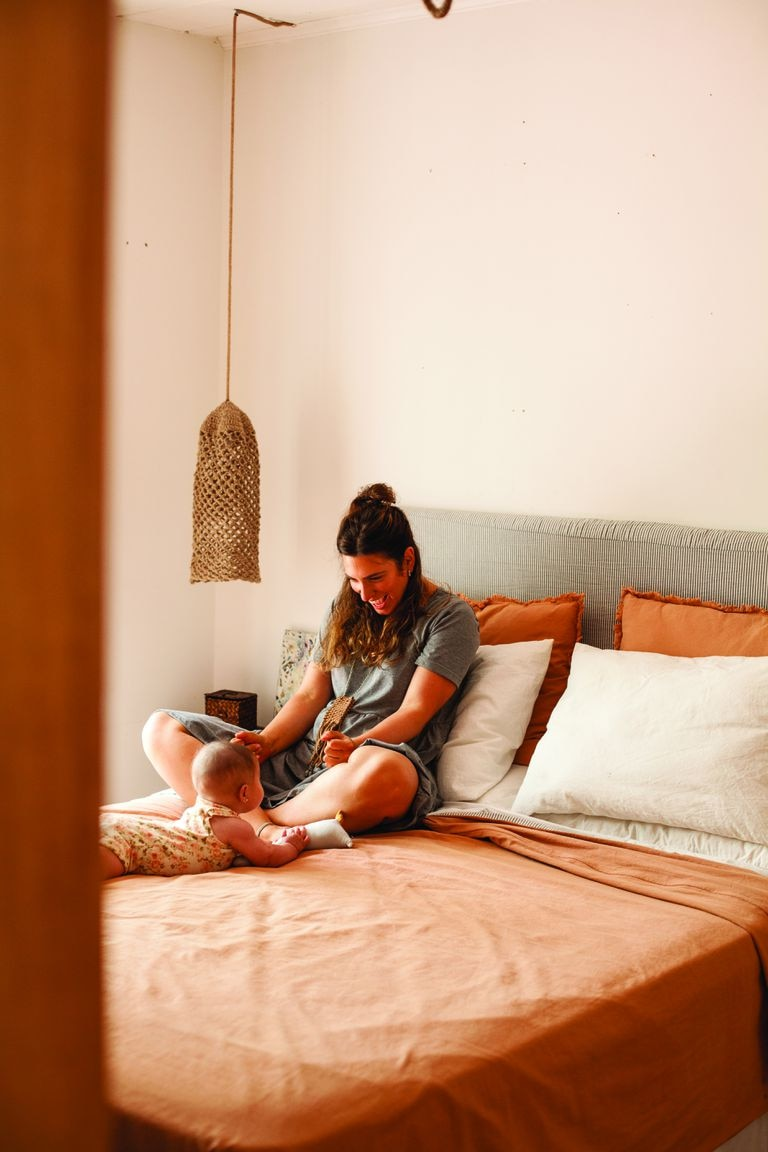 """Para el dormitorio principal, Nadia eligió todo reversible porque se aburre rápido. Eligió una combinación verde seco y terracota que es más """"campo"""" y después sumó rayas en gris y blanco para verano, porque es más playero. La lámpara hecha a mano es de Vero Alessandrini."""