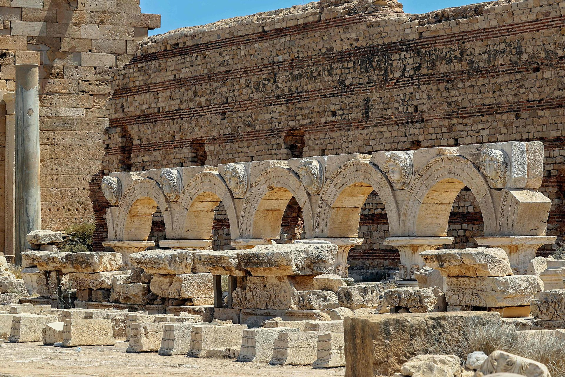 Una imagen muestra arcos con cabezas de gorgona talladas que rodean el foro de Severin, en la antigua ciudad romana de Leptis