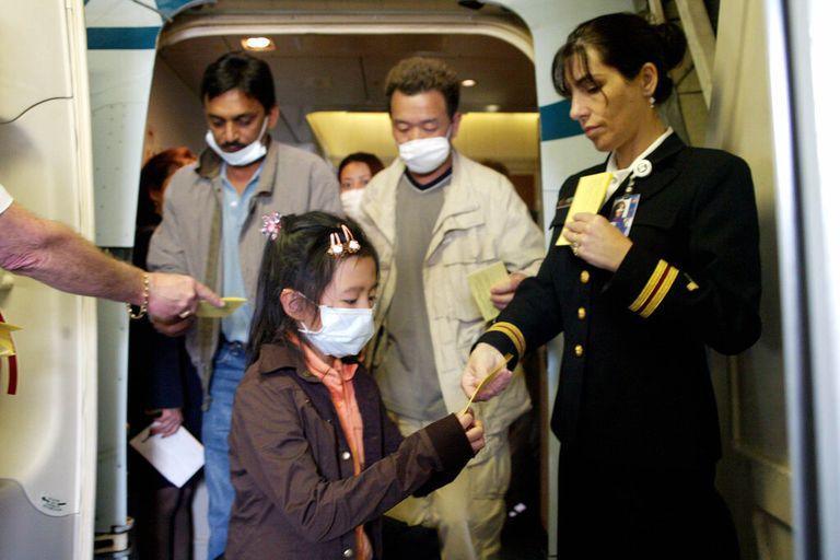 Pasajeros con cubrebocas que llegaron a Los Ángeles procedentes de Hong Kong durante el brote del SARS en 2003, recibieron folletos en los que se les aconsejaba vigilar su salud durante 10 días