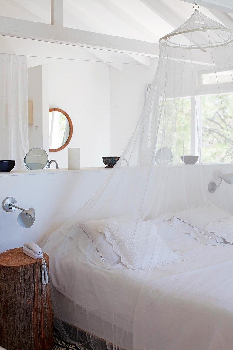Su habitación, blanca, con pocos muebles y toques rústicos, resulta perfecta para una casa de verano.
