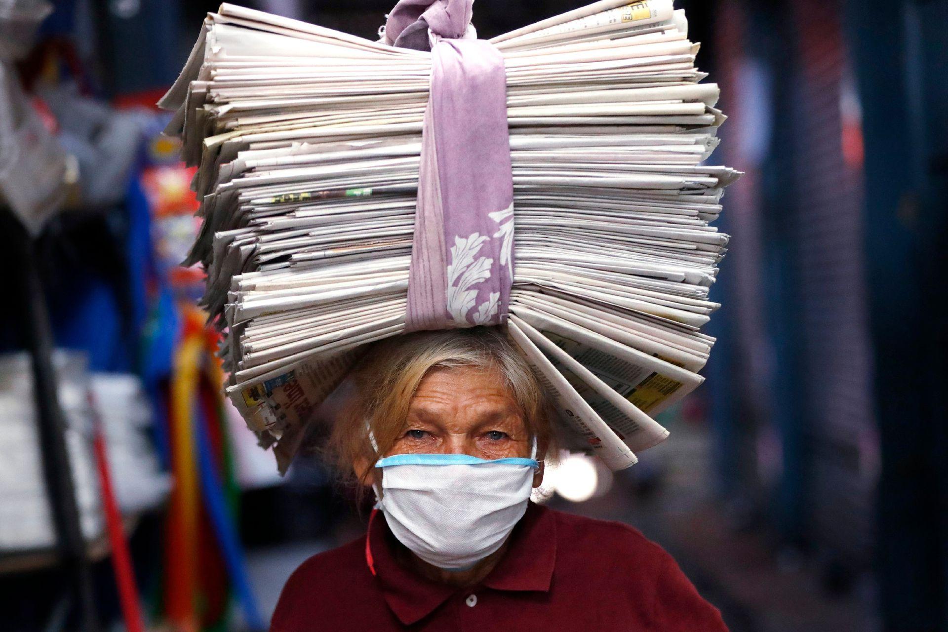Guillermina de Figueredo, de 72 años, balancea periódicos reciclados en su cabeza que vende a comerciantes que los usan como envoltorios